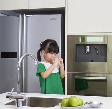 Healthy kid drinking from home water dispenser
